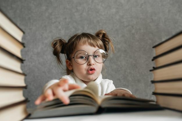 Gelukkig grappig kaukasisch meisje dat in glazen een boek leest.