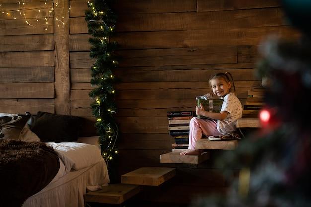 Gelukkig grappig kind meisje met geschenken in bed kerstochtend