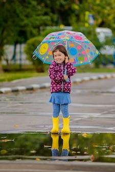 Gelukkig grappig kind met veelkleurige paraplu springen plassen in rubberen laarzen en lachen