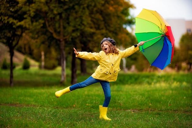 Gelukkig grappig kindmeisje met veelkleurige paraplu in rubberlaarzen bij herfstpark.