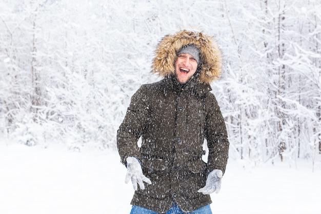 Gelukkig grappig mannelijk portret op zoek naar sneeuwvlokken die naar beneden vallen.