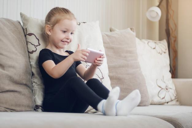 Gelukkig grappig meisjesspel op smartphone. kind kijken naar online tekenfilms, computerverslaving voor kinderen, ouderlijk toezicht. afstandsonderwijs, online onderwijs voor kinderen.