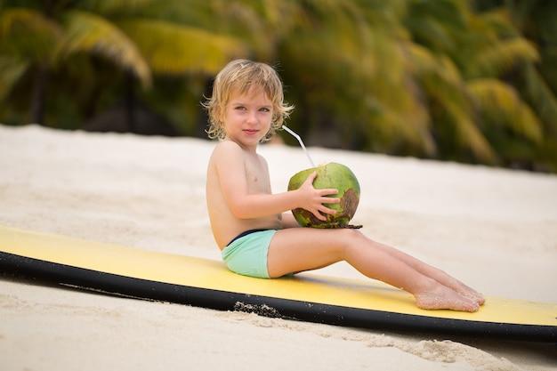 Gelukkig grappig weinig peuterjong geitjejongen die kokossap op oceaanstrand drinken.