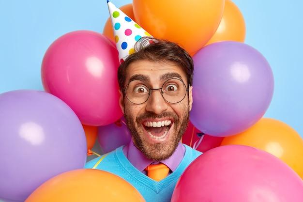 Gelukkig grappige kerel omringd door partij ballonnen poseren