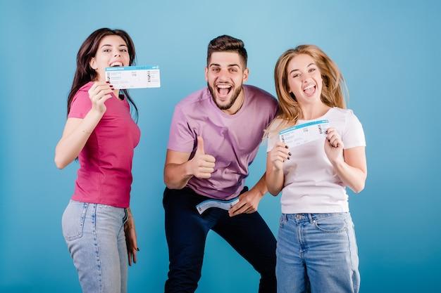 Gelukkig groep vrienden man en vrouw met vliegtickets op blauw