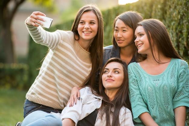 Gelukkig groep vrouwelijke studenten zitten in het park.