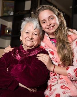 Gelukkig grootmoeder en kleindochter poseren thuis