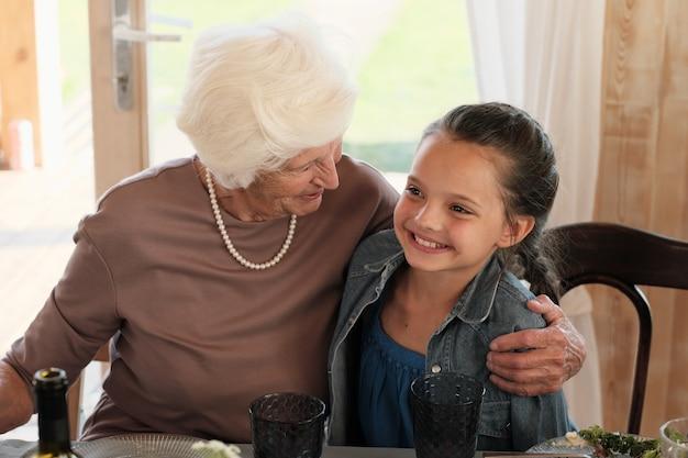 Gelukkig grootmoeder omhelst haar lachende kleindochter terwijl ze aan tafel zitten en thuis eten