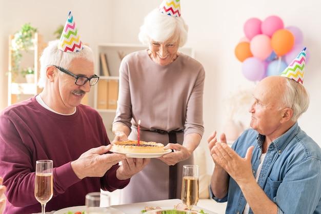 Gelukkig grootmoeder zoete zelfgemaakte taart met brandende kaars brengen naar senior mannen