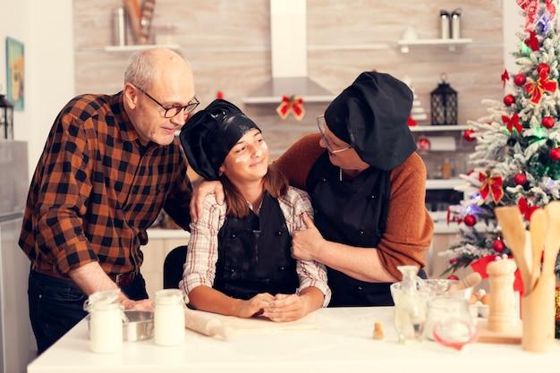 Gelukkig grootouder en kind op eerste kerstdag dessert maken