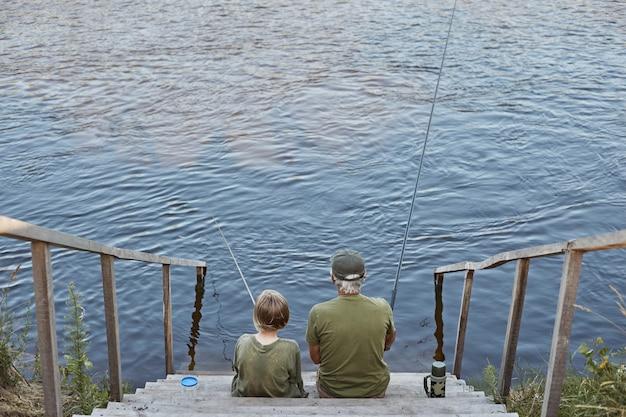 Gelukkig grootvader en kleinzoon vissen samen, zittend op houten plaatsen in de buurt van rivier, hengel in handen houden