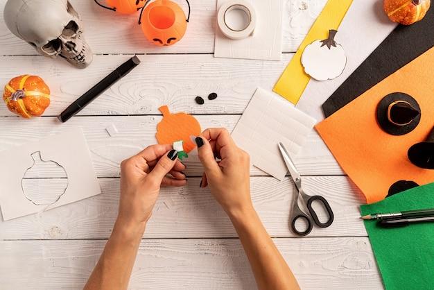 Gelukkig halloween-concept. stap voor stap instructie voor het maken van halloween-bladwijzer diy-pompoenambachten. stap 5 - blijf bij elkaar. bovenaanzicht plat liggend
