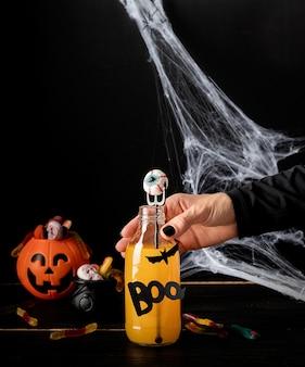 Gelukkig halloween-concept. vrouwenhand met zwarte spijkers die enge kleurrijke halloween-cocktail met partijdecoratie op donkere achtergrond houden