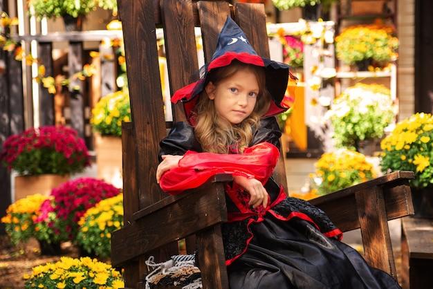 Gelukkig halloween een meisje in een heksenkostuum met een pompoen die plezier heeft in de herfst in de buurt van het huis