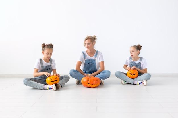 Gelukkig halloween en vakantieconcept - een moeder en haar dochters met pompoenen. gelukkig gezin