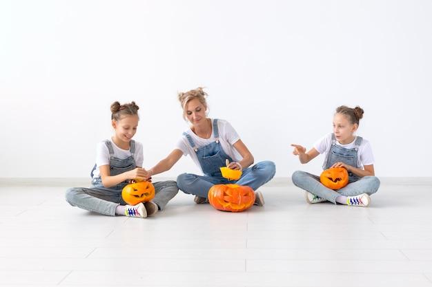 Gelukkig halloween en vakantieconcept - een moeder en haar dochters met pompoenen. gelukkige familie halloween voorbereiden.