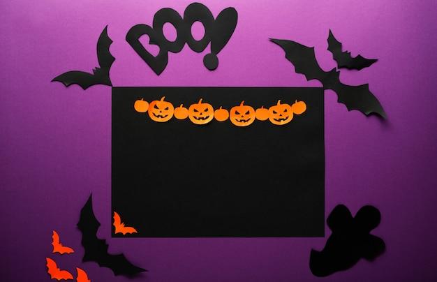 Gelukkig halloween-frame. spinnen vleermuizen spook oranje papier jack o'lantern pompoenen op perple achtergrond