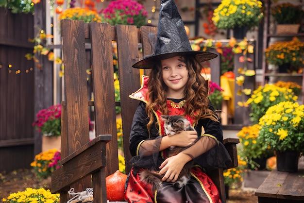 Gelukkig halloween-meisje in heksenkostuums die plezier hebben in de herfst in de buurt van het huis