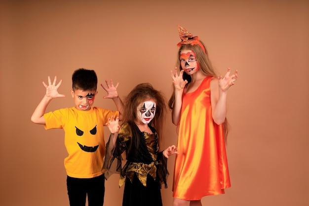 Gelukkig halloween-portret van kinderen in kostuums op een beige muur