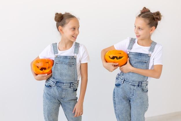 Gelukkig halloween, vakantie en jeugdconcept - schattige kleine tweelingzusjes meisjes met een pompoenen jack-o'-lantern plezier terwijl ze tijd binnenshuis doorbrengen.