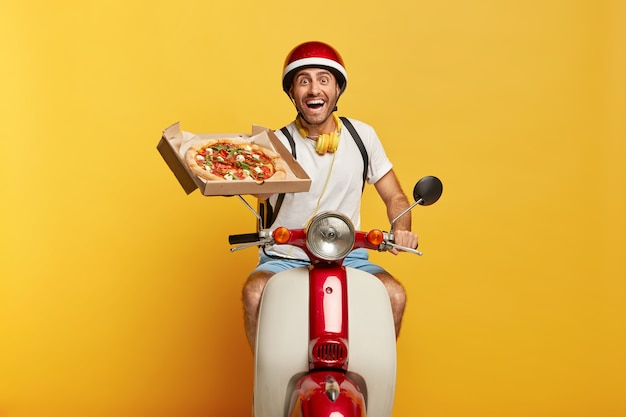 Gelukkig hardwerkende knappe mannelijke bestuurder op scooter met rode helm die pizza levert