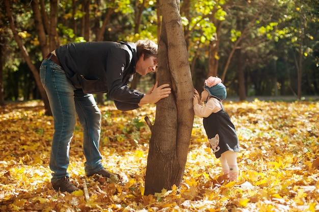 Gelukkig herfst. vader en dochter spelen verstoppertje