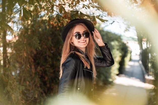 Gelukkig herfstportret van een mooie jonge vrouw met een glimlach in modieuze zwarte kleding met een hoed loopt buiten op een zonnige dag