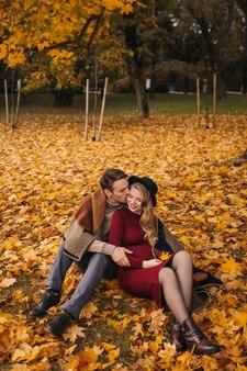 Gelukkig heteroseksueel paar zit op de grond bedekt met gele bladeren op de herfstdag knappe man...