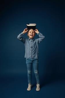 Gelukkig hier te zijn. klein meisje of kind in jeans en shirt met virtual reality headset bril geïsoleerd op blauwe studio achtergrond. concept van geavanceerde technologie, videogames, innovatie.