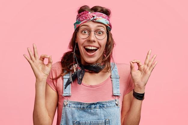 Gelukkig hippievrouw maakt oke gebaar, houdt van vriend's plan, draagt stijlvolle kleding, heeft vrolijke gezichtsuitdrukking, geïsoleerd over roze muur. hippievrouw klaar voor iets