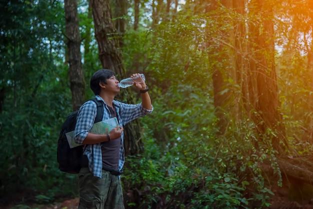 Gelukkig hipster man toerist met rugzak drinkwater terwijl wandelen in de natuur bos.