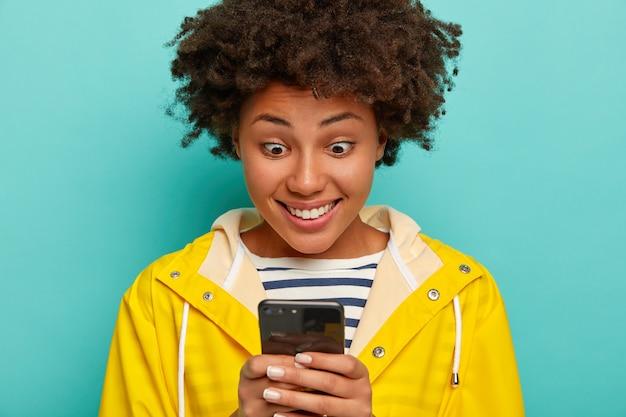 Gelukkig hipster meisje met verbaasde blik, aangenaam sms-bericht leest, geniet van chatten, draagt gele regenjas geïsoleerd op blauwe muur