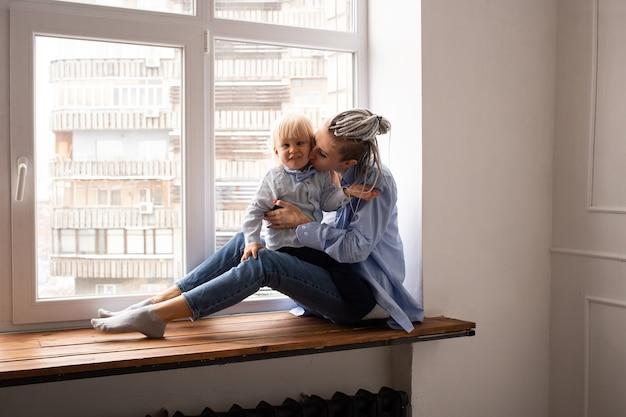 Gelukkig hipster moeder en jongenskind zittend op venster in quarantaine