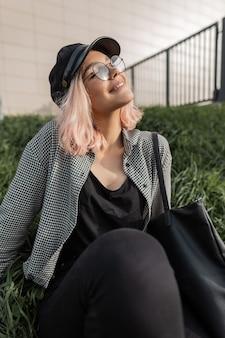 Gelukkig hipster tienermeisje met een glimlach in modieuze vintage kleding met een tas en bril zit op het gras in de stad