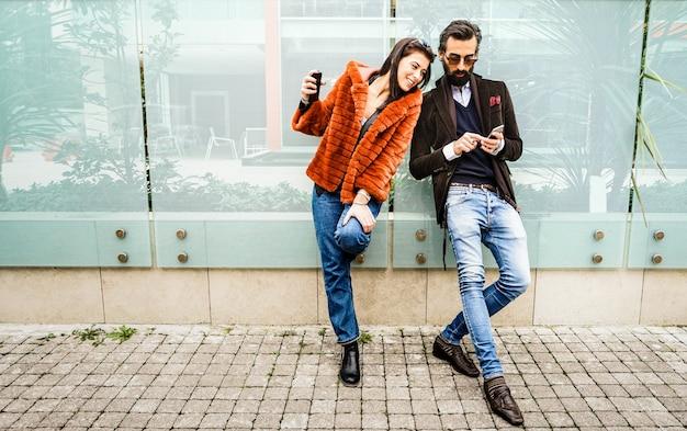 Gelukkig hipsterpaar die pret met hun smarphones hebben in openlucht bij