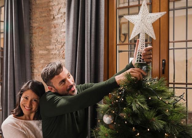 Gelukkig hoger paar dat de kerstmisboom verfraait