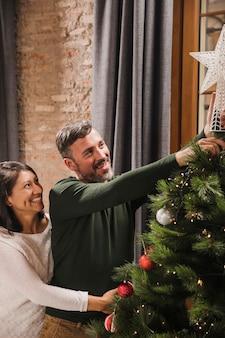 Gelukkig hoger paar dat dichtbij de kerstmisboom glimlacht