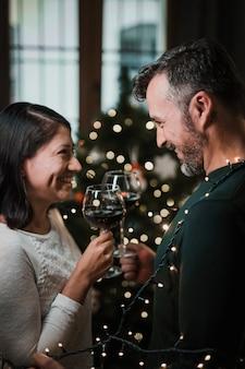Gelukkig hoger paar dat dichtbij de kerstmisboom toejuicht