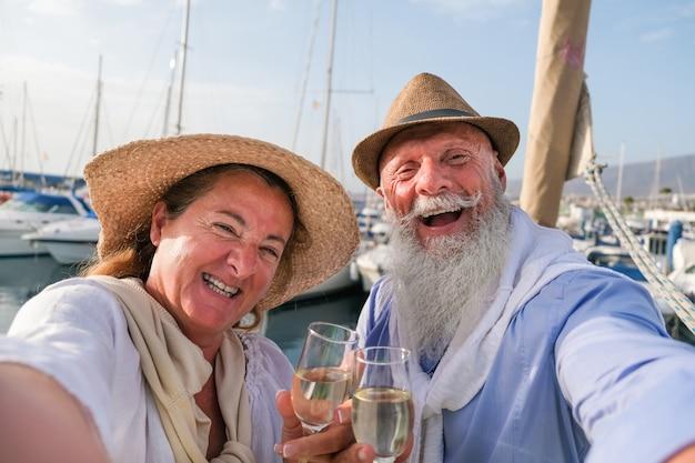Gelukkig hoger paar dat selfie doet, toejuichend met champagne op een zeilboot tijdens verjaardagsvakantie