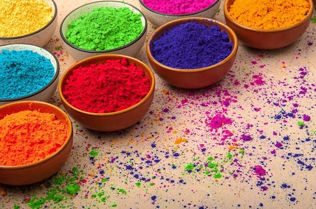 Gelukkig holi-bovenaanzicht van kleurrijke holi-kleuren in kommen met splash, concept indisch kleurenfestival.