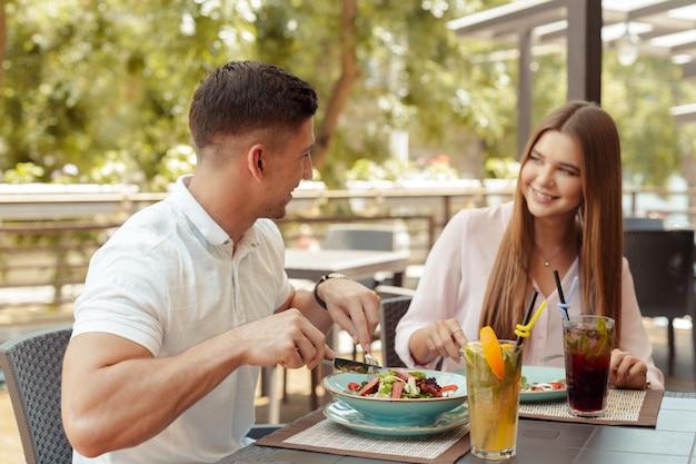 Gelukkig houdend van paar die van ontbijt in een koffie genieten.