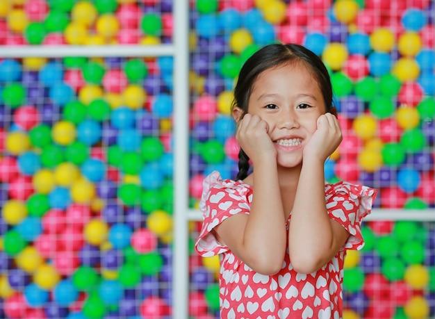 Gelukkig houdt weinig aziatisch kindmeisje beide handen op wangen tegen kleurrijke balspeelplaats. charmant en positief uitziend. drukt aangename emoties uit.