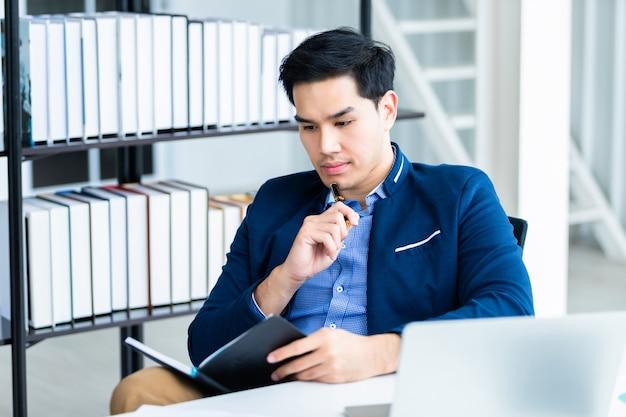 Gelukkig humeur een vrolijk van aziatische jonge zakenman die werkt met het maken van aantekeningen in een notebook en laptopcomputer in de kantoorruimte.