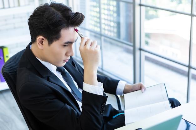 Gelukkig humeur een vrolijke van aziatische jonge zakenman ideeën hebben, noteer het succesvolle businessplan in een notebook en computer op houten tafel achtergrond in kantoor.