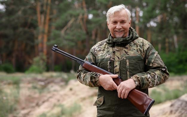 Gelukkig hunter old man in camouflage met shotgun.