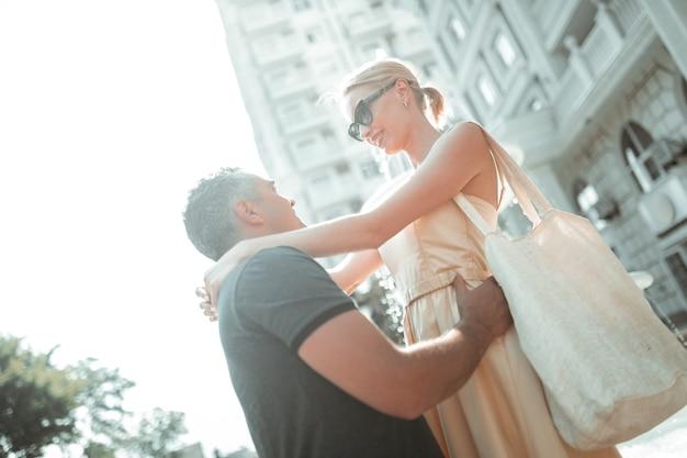 Gelukkig huwelijk. vrolijke man en vrouw knuffelen elkaar in de ogen kijken en buiten glimlachen.