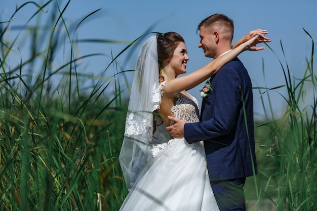 Gelukkig huwelijkspaar die op houten brug lopen. emotionele bruid en bruidegom knuffelen zachtjes buitenshuis.