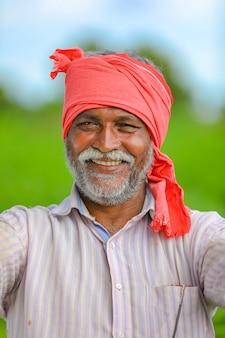 Gelukkig indiase boer op groen katoen veld