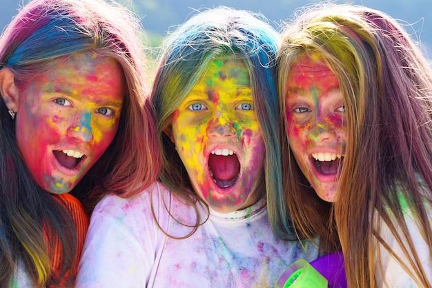 Gelukkig jeugdfeest. optimist. spring vibes. kinderen met creatieve lichaamskunst. gekke hipster meisjes. zomerweer. positief en vrolijk. kleurrijke neonverfmake-up. kleurrijke make-up. holi make-up.