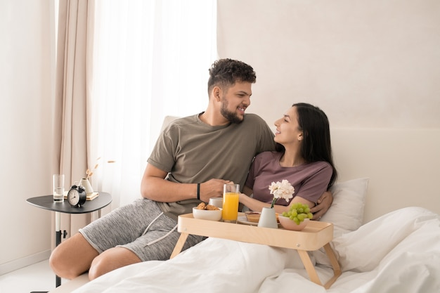 Gelukkig jong aanhankelijk stel dat elkaar met een glimlach aankijkt terwijl ze in bed zitten, lekker ontbijten en iets leuks bespreken